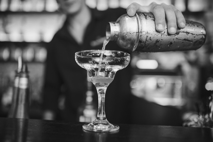 Barkeeper kippt einen Gin-Cockatil in eine Cocktail Schale