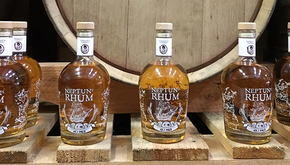 Neptuns Rhum Flaschen vor Holzfass