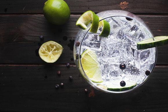 Gin Tonic mit Limette, Gurke und Wacholder auf schwarzen Holztisch