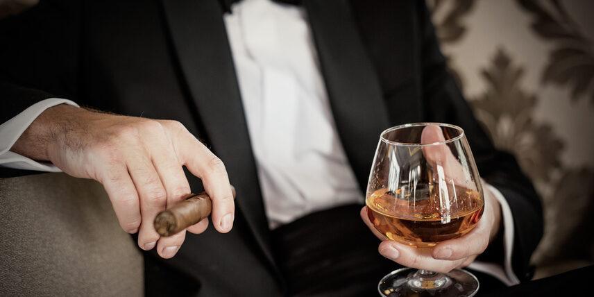 Gentleman hält Glas mit Cognac und eine Zigarre
