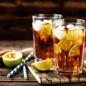 Cuba Libre or long island iced tea cocktail with strong drinks, cola, lime and ice in glass, cold longdrink