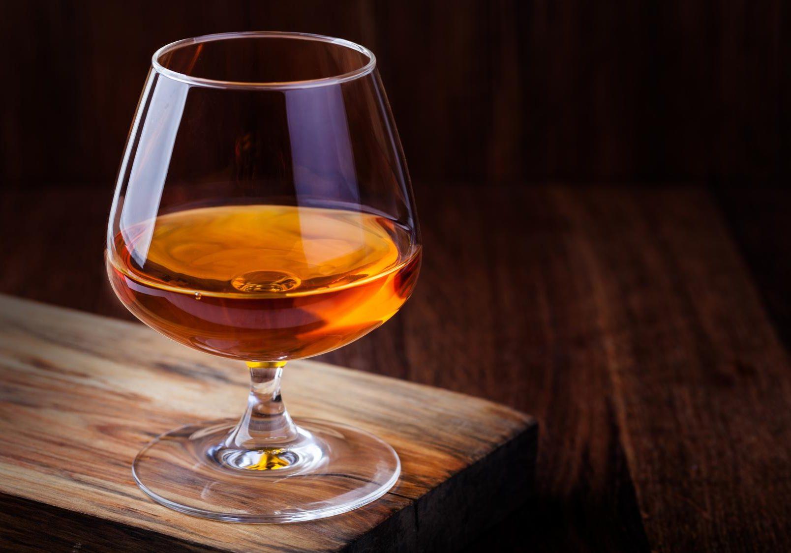 Glas Cognac auf hözernem Tisch